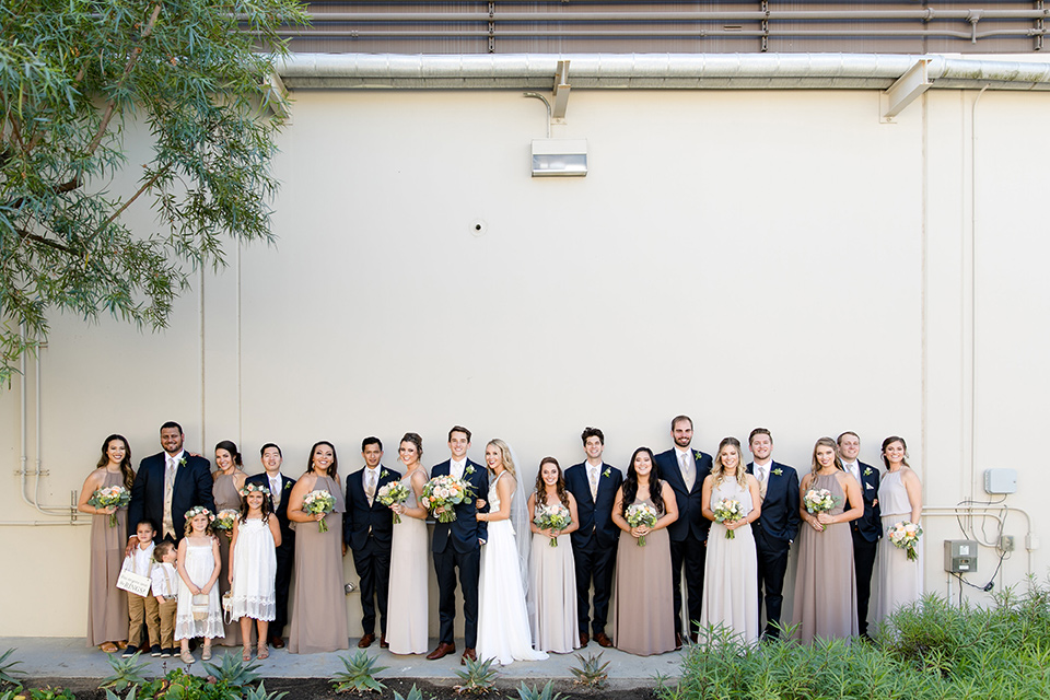 callaway-winery-wedding-party-in-a-line-by-white-wall-bride-in-a-flowing-white-gown-with-straps-and-a-deep-v-neckline-groom-in-a-navy-blue-suit-bridesmaids-in-taupe-and-nude-gowns-the-groomsmen-in-navy-blue-suits