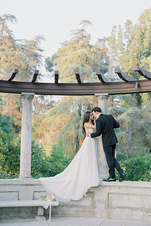 Kimberly-crest-house-shoot-bride-and-groom-kissing-standing-groom-in-a-traditional-black-tuxedo-with-white-shirt-and-black-bow-tie-bride-in-a-modern-princess-inspired-flowing-white-gown-with-a-full-skirt