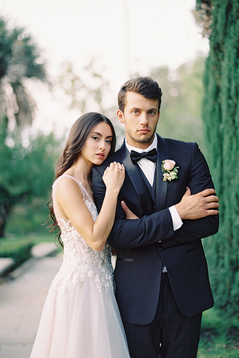 Kimberly-crest-house-shoot-bride-and-groom-looking-at-camera-groom-in-a-black-tuxedo-with-white-shirt-and-black-bow-tie-bride-in-a-flowing-white-gown-with-a-full-skirt