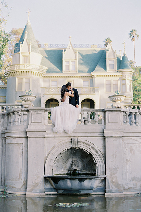Kimberly-crest-house-shoot-bride-and-groom-sitting-on-venue-bridge-with-pond-groom-in-a-traditional-black-tuxedo-with-white-shirt-and-black-bow-tie-bride-in-a-modern-princess-inspired-flowing-white-gown-with-a-full-skirt