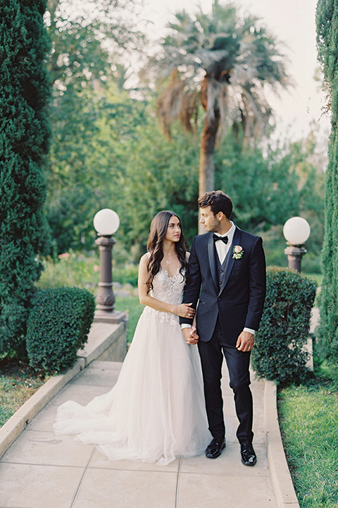 Kimberly-crest-house-shoot-bride-and-groom-walking-down-path-groom-in-a-traditional-black-tuxedo-with-white-shirt-and-black-bow-tie-bride-in-a-modern-princess-inspired-flowing-white-gown-with-a-full-skirt