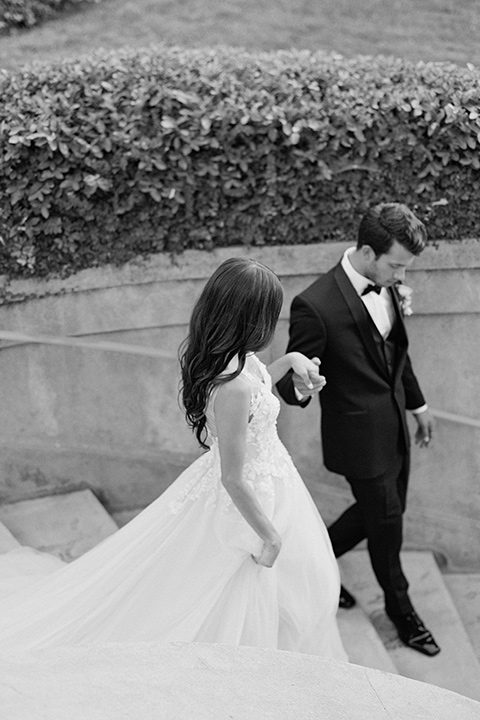 Kimberly-crest-house-shoot-bride-and-groom-walking-down-the-stairs-groom-in-a-black-tuxedo-with-white-shirt-and-black-bow-tie-bride-in-a-flowing-white-gown-with-a-full-skirt