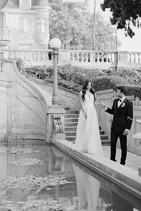 Kimberly-crest-house-shoot-groom-holding-brides-hand-by-pond-groom-in-a-black-tuxedo-with-white-shirt-and-black-bow-tie-bride-in-a-flowing-white-gown-with-a-full-skirt