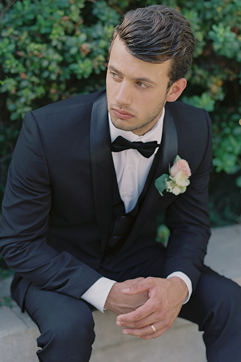 Kimberly-crest-house-shoot-groom-sitting-in-a-black-tuxedo-with-white-shirt-and-black-bow-tie