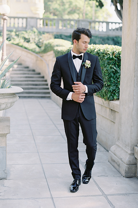 Kimberly-crest-house-shoot-groom-walking-in-a-traditional-black-tuxedo-with-white-shirt-and-black-bow-tie