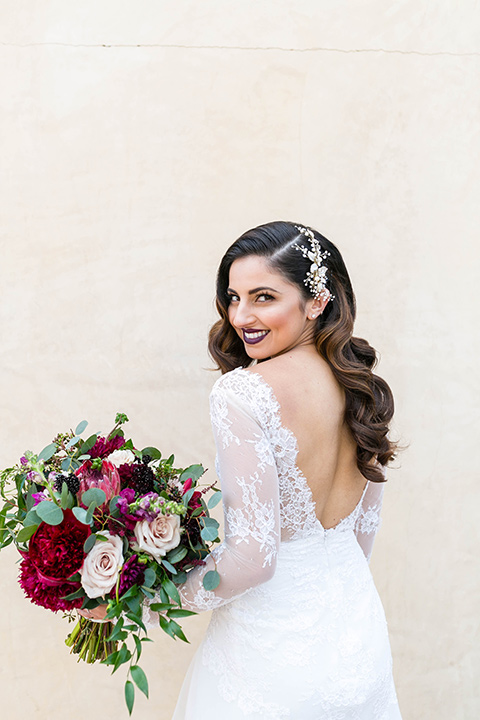 bride in a white lace gown with a full skirt and long lace sleeves and her hair in a finger wave
