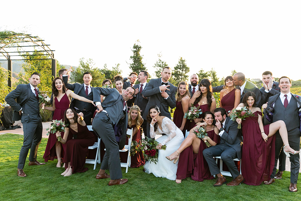 bride in a white lace gown with a full skirt and long lace sleeves and her hair in a finger wave and the groom in a charcoal tuxedo with a black bow tie and the groomsmen in charcoal tuxedo and bridesmaids in burgundy gowns