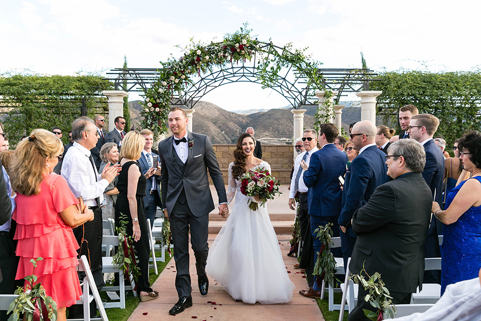 bride in a white lace gown with a full skirt and long lace sleeves and her hair in a finger wave and the groom in a charcoal tuxedo