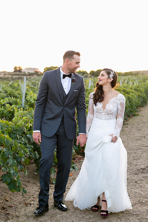 bride in a white lace gown with a full skirt and long lace sleeves and her hair in a finger wave and the groom in a charcoal tuxedo with a black bow tie