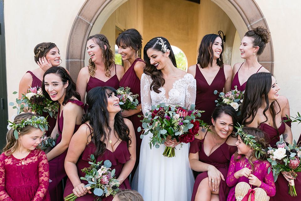 bride in a white lace gown with a full skirt and long lace sleeves and her hair in a finger wave and the bridesmaids in burgundy gowns