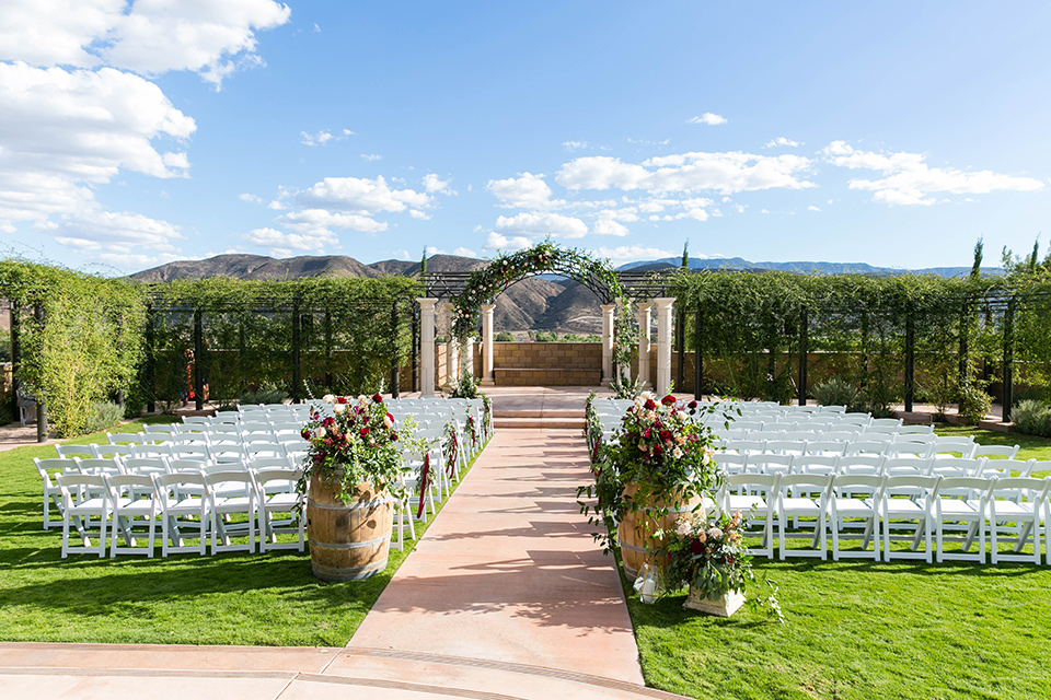 white wooden chairs and colorful florals with vineyards in the background