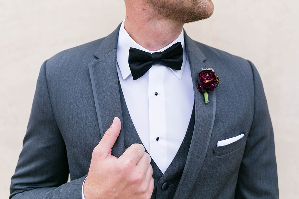 the groom in a charcoal tuxedo with a black bow tie