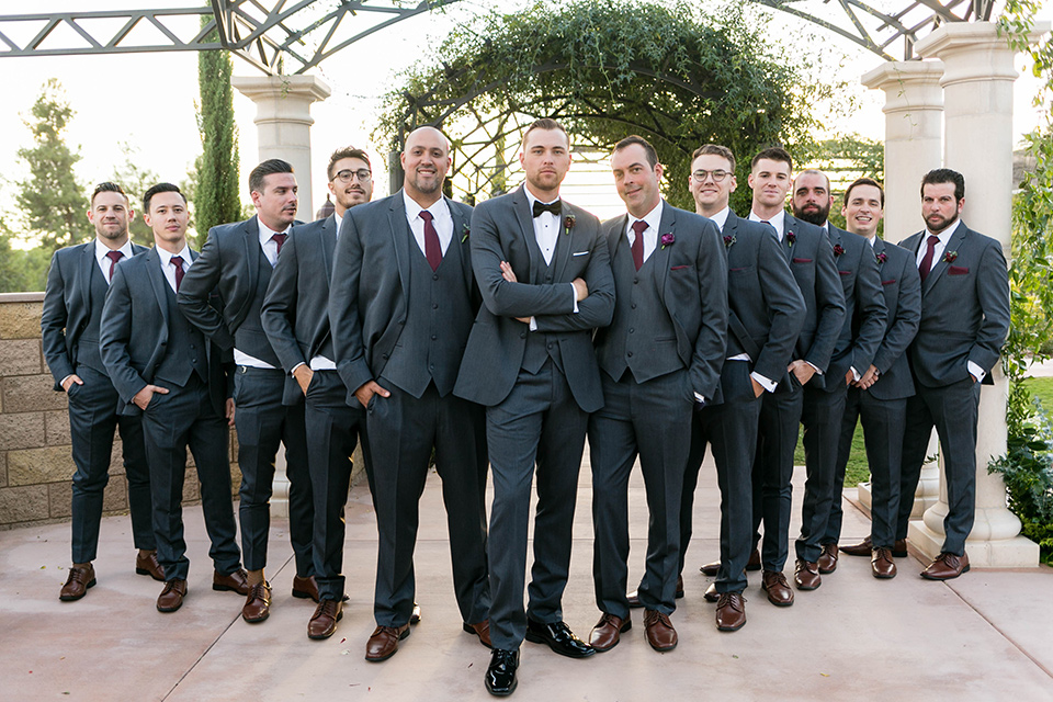 groom in a charcoal tuxedo with a black bow tie and the groomsmen in charcoal tuxedo