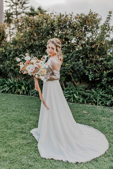 bride in a white gown with an illusion neckline hair in a loose curl