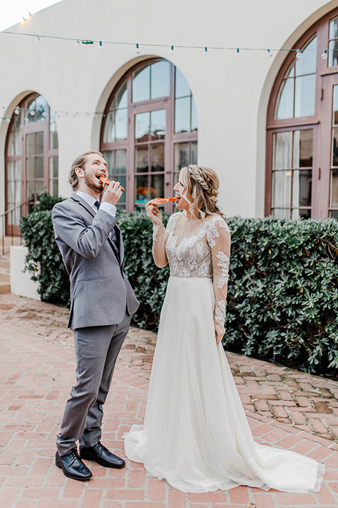 bride in a white gown with an illusion neckline hair in a loose curl, groom in a grey suit with a black trim and long black tie