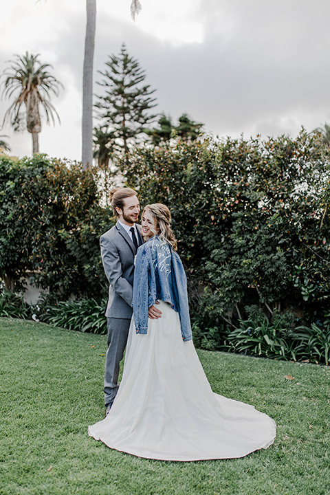 bride and groom holding each other, the bride in a white lace gown with a jean jacket and the groom in a grey suit with black trim and black long tie