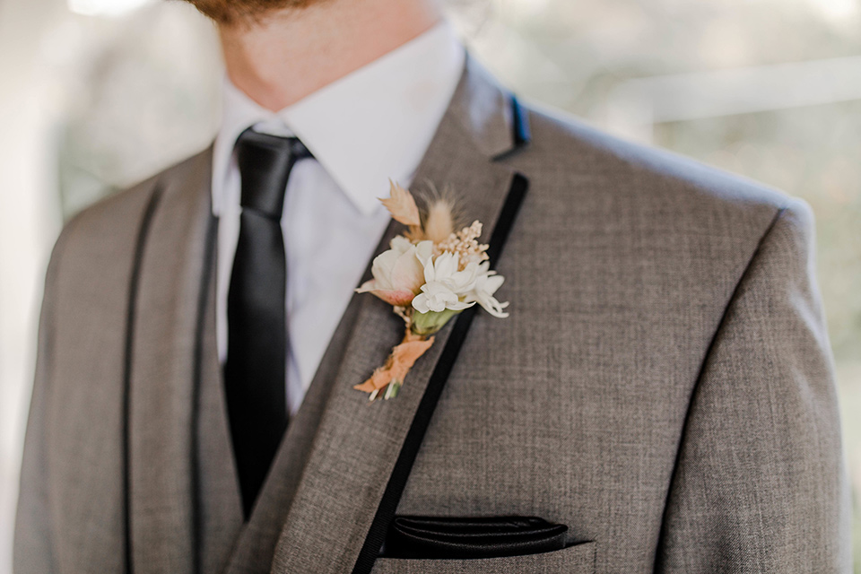 groom in a grey suit with black trim and black long tie
