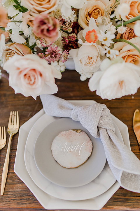 white plates with gold trim and gold flatware