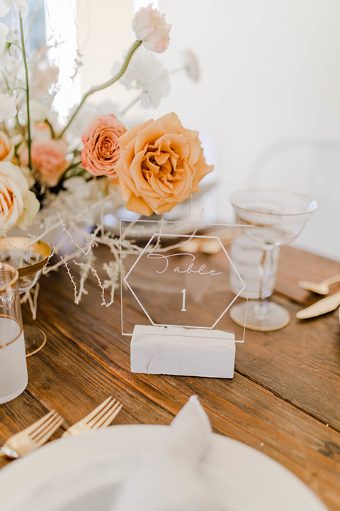 wooden table with white plates and gold deco