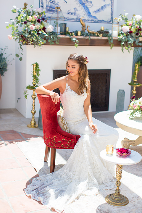 bride in a white lace gown with thin straps and a white and red floral bouquet sitting in a red chair
