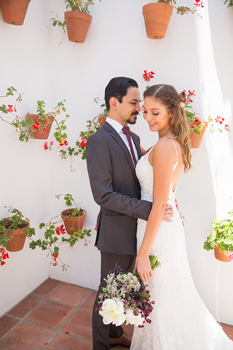 bride in a white lace gown with thin straps and a white and red floral bouquet and the groom in a grey suit with a red long tie