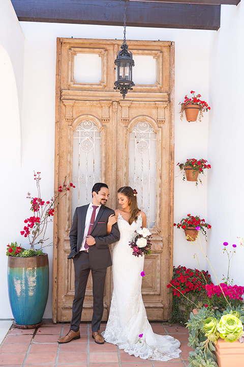 bride in a white lace gown with thin straps and a white and red floral bouquet and the groom in a grey suit with a red long tie by wooden door
