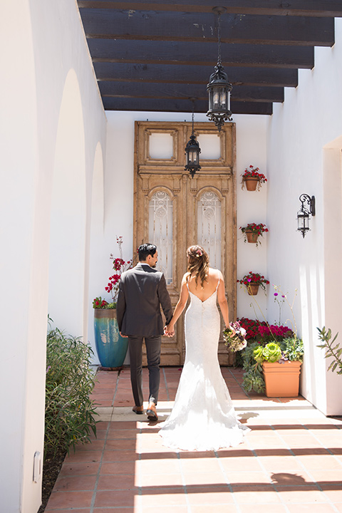 bride in a white gown with thin straps and lace detailing and the groom in a grey suit with a red long tie walking away