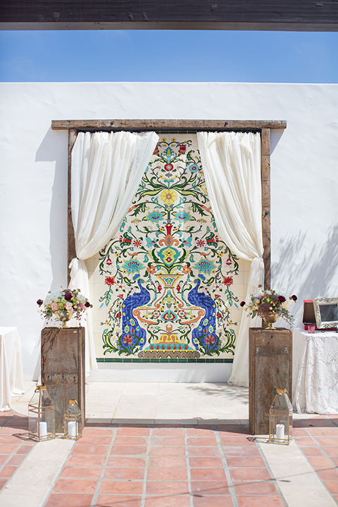 ceremony arch with wood and white flowing linens and colorful tile wall behind them