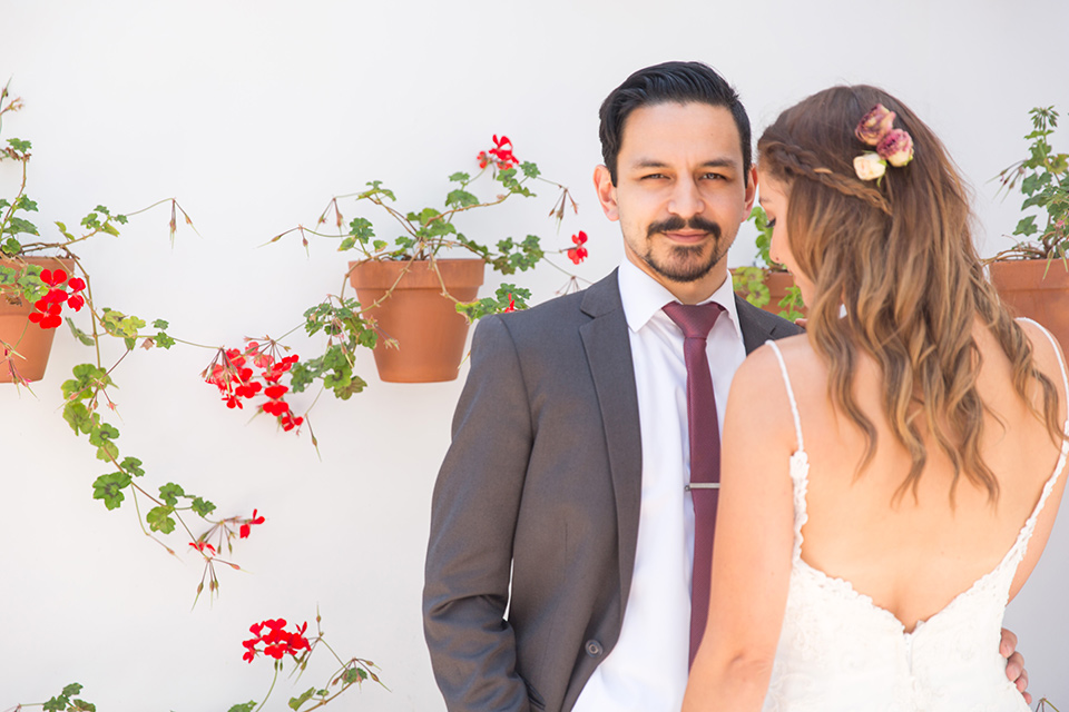 bride in a white lace with straps and the groom in a grey suit with a red long tie