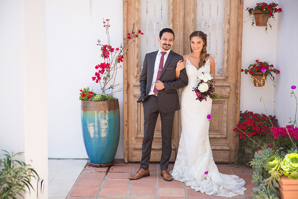 groom in a grey suit with a red long tie and the bride in a white lace gown with thin straps