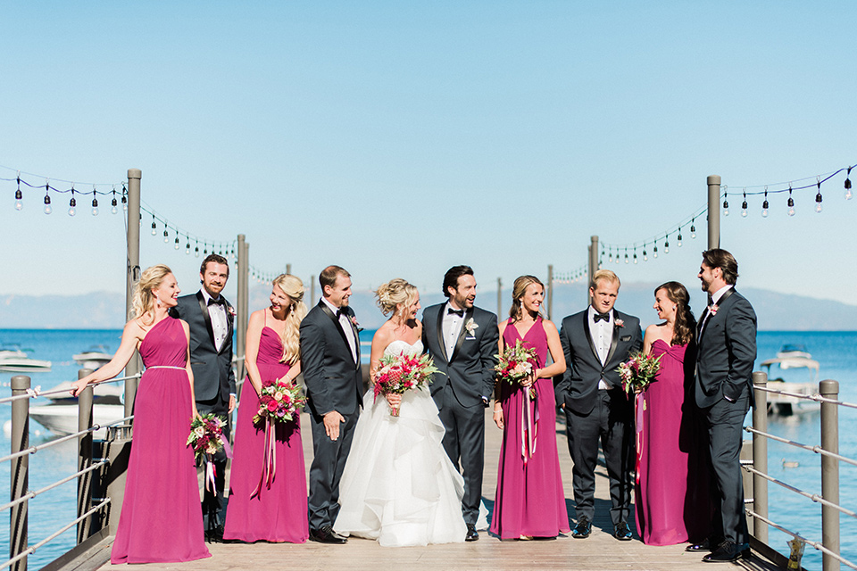 The wedding party poses for photos on a dock in lake tahoe
