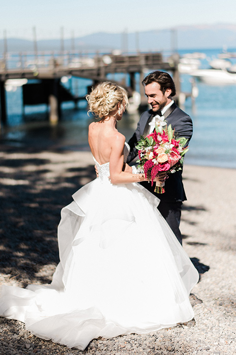Bride and groom embrace in a photo on the lake