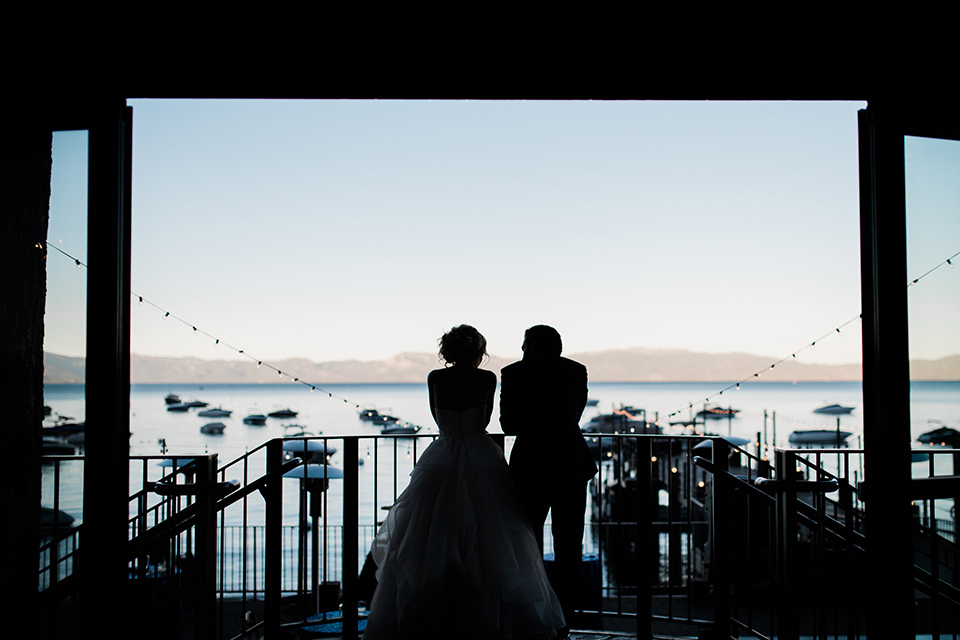Lake Tahoe wedding bride and groom looking out window bride in a white tulle ballgown with white tulle ballgown with a strapless dresswith a strapless neckline the groom wore a navy shawl lapel tuxedo with black trim and a black bow tie