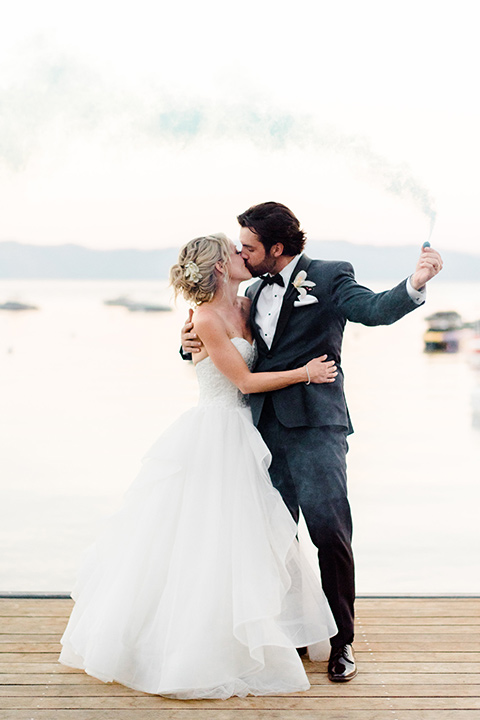 Lake Tahoe wedding bride and groom taking a selfie bride is in a strapless ballgown with a tulle skirt and the groom in a navy shawl lapel tuxedo with a black bow tie-bow-tie