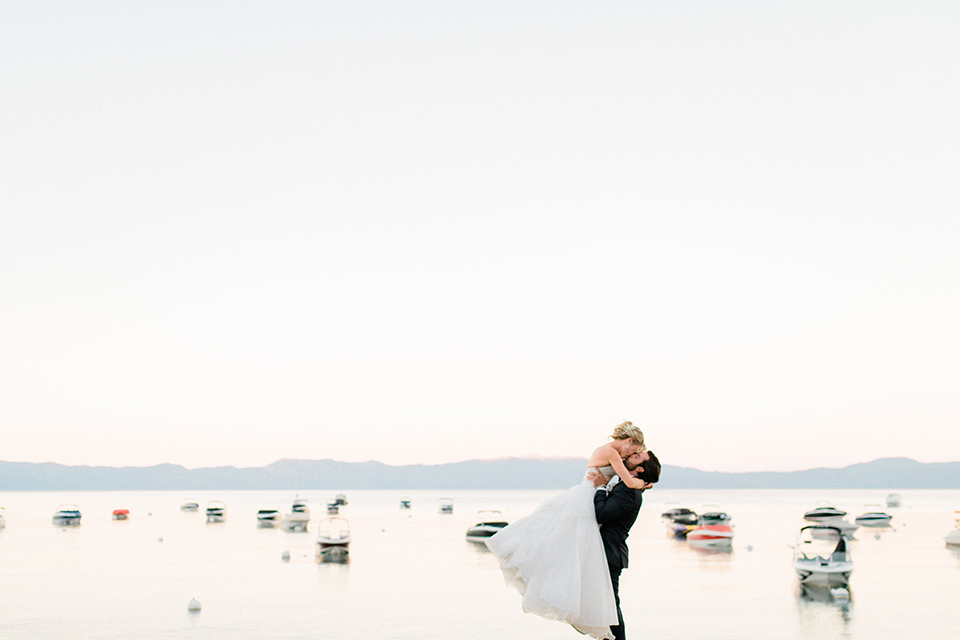 Bride and groom pose for a kiss with the lake in the background
