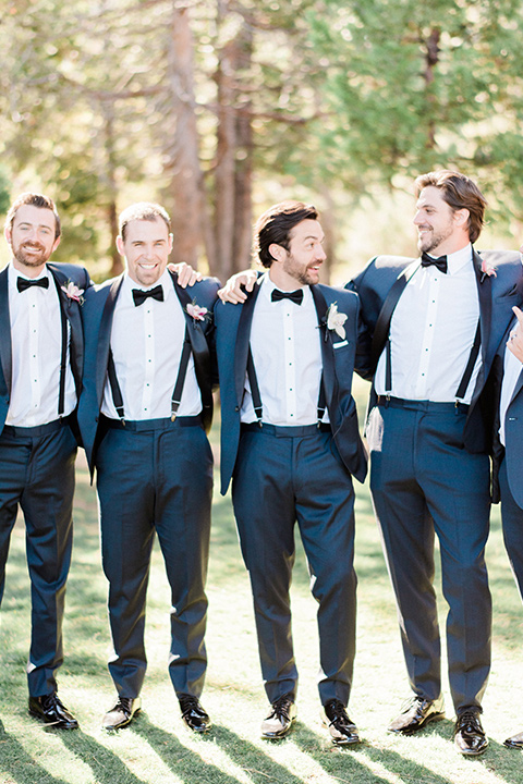 groomsmen with jackets unbuttoned in navy shawl lapel tuxedos with a black bow ties
