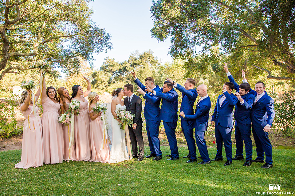 mount-woodson-castle-bridal-party-in-a-line-bridesmaids-in-light-pink-long-dresses-groomsmen-in-cobalt-blue-suits-with-pink-ties-bride-in-a-mermaid-gown-with-lace-detailing-and-a-sweetheart-neckline-groom-in-a-lack-suti-with-a-black-long-tie