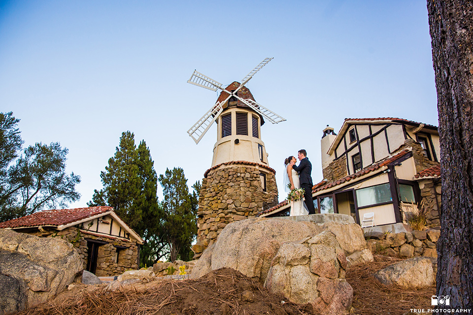 mount-woodson-castle-bride-and-groom-at-windmill-bride-in-a-mermaid-gown-with-lace-detailing-and-a-sweetheart-neckline-groom-in-a-black-suti-with-a-black-long-tie