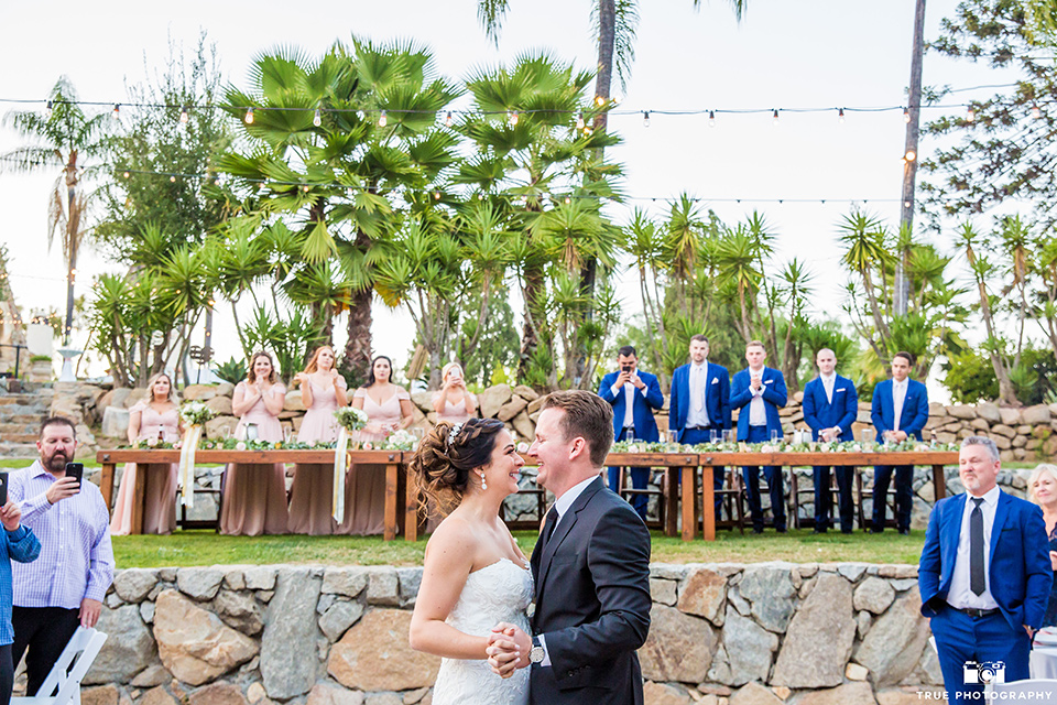 mount-woodson-castle-bride-and-groom-first-dance-bridesmaids-in-light-pink-long-dresses-groomsmen-in-cobalt-blue-suits-with-pink-ties-bride-in-a-mermaid-gown-with-lace-detailing-and-a-sweetheart-neckline-groom-in-a-lack-suti-with-a-black-long-tie