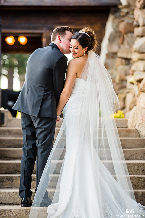 mount-woodson-castle-bride-and-groom-kissing-on-steps-bride-in-a-lace-strapless-gown-with-a-sweetheart-neckline-groom-in-a-black-suit-with-long-black-tie