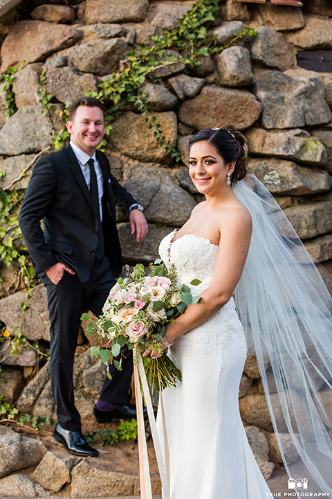 mount-woodson-castle-bride-and-groom-smiling-on-camera-groom-in-a-charcoal-suit-with-a-black-long-tie-bride-in-a-white-lace-gown-with-a-strapless-neckline