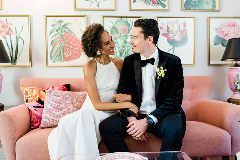 malibu-lodge-spring-wedding-shoot-bride-and-groom-on-pink-couch-bride-in-a-flowing-form-fittting-gown-with-a-high-necklink-groom-in-a-black-velvet-tuxedo-with-a-black-bow-tie