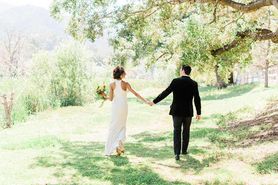 malibu-lodge-spring-wedding-shoot-bride-and-groom-walking-away-from-camera-bride-in-a-flowing-form-fittting-gown-with-a-high-necklink-groom-in-a-black-velvet-tuxedo-with-a-black-bow-tie