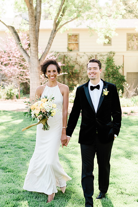 malibu-lodge-spring-wedding-shoot-bride-and-groom-walking-bride-in-a-form-fitting-gown-with-a-high-neckline