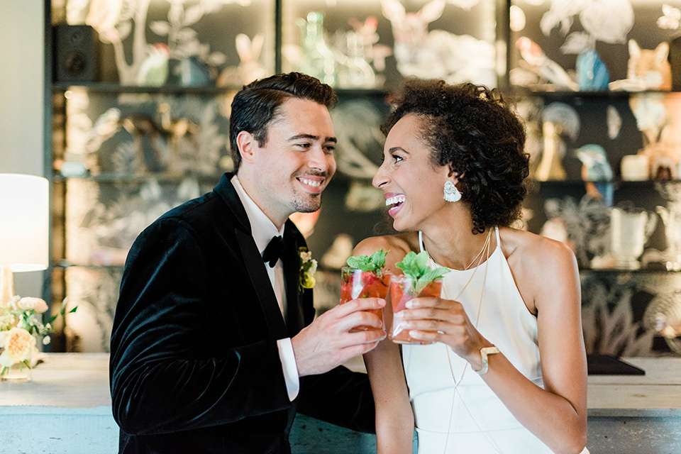 malibu-lodge-spring-wedding-shoot-bride-and-groom-with-drinks-bride-in-a-flowing-form-fittting-gown-with-a-high-necklink-groom-in-a-black-velvet-tuxedo-with-a-black-bow-tie