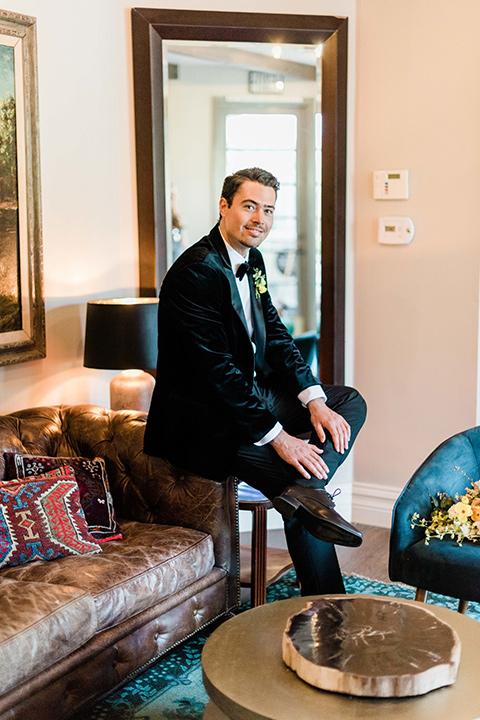 malibu-lodge-spring-wedding-shoot-groom-sitting-in-a-black-velvet-tuxedo