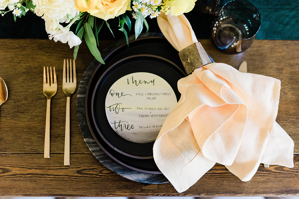 malibu-lodge-spring-wedding-shoot-plates-with-black-plates-and=gold-tableware-and-pink-napkins