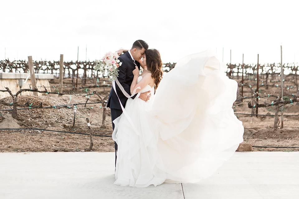Lorimar-winery-shoot-bride-and-groom-holding-each-other-brides-dress-flowing-in-the-breeze-bride-in-a-ballgown-with-flowing-tulle-and-a-sweetheart-neckline-groom-in-a-navy-suit-with-a-blue-tie