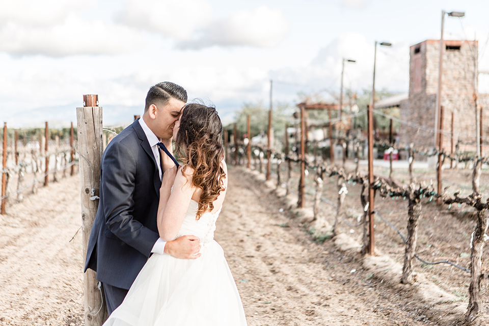 Lorimar-winery-shoot-bride-and-groom-kissing-bride-in-a-ballgown-with-flowing-tulle-and-a-sweetheart-neckline-groom-in-a-navy-suit-with-a-blue-tie