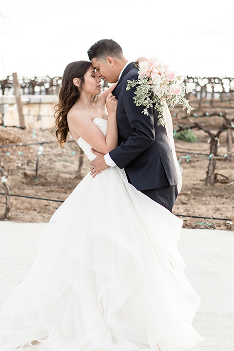 Lorimar-winery-shoot-bride-and-groom-touching-heads-bride-in-a-tulle-ballgown-and-groom-in-a-navy-suit-with-blue-tie
